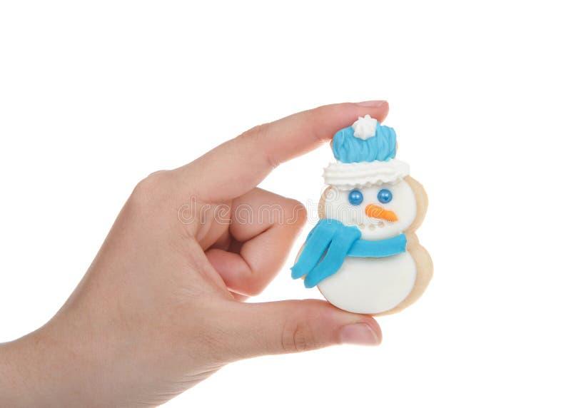 Dé sostener la galleta de azúcar a casa hecha del muñeco de nieve aislada fotografía de archivo