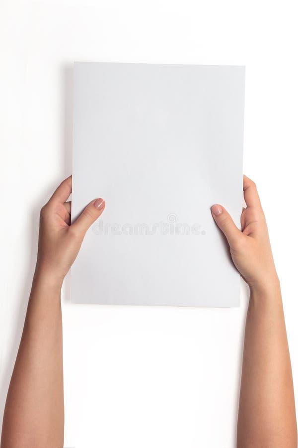 Dé sostener la maqueta blanca de la hoja del papel en blanco, aislada Mofa de la plantilla del folleto del claro del control del  fotografía de archivo