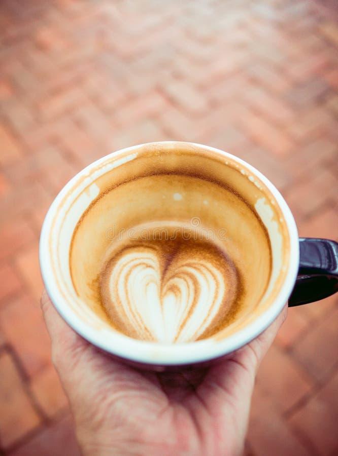 Dé sostener la media taza de café caliente de la leche en el latte AR de la forma del corazón foto de archivo
