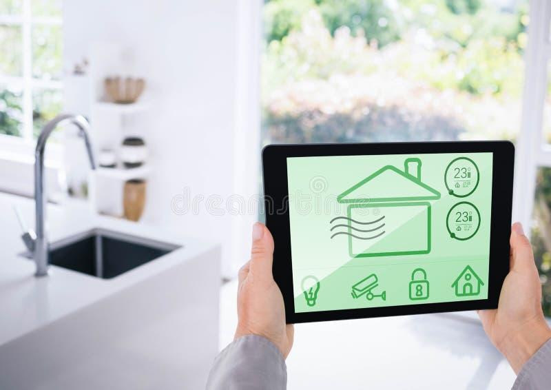 Dé sostener la tableta digital con los iconos de la seguridad en el hogar en la pantalla imagen de archivo