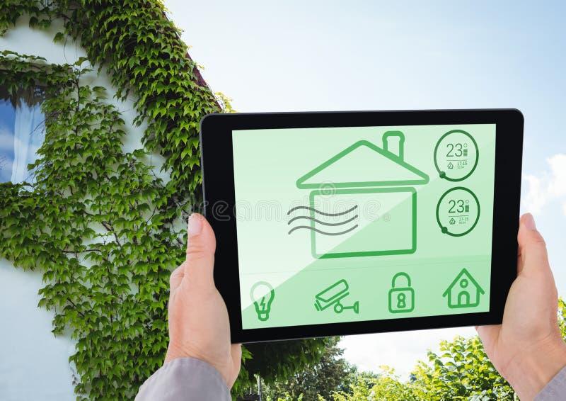 Dé sostener la tableta digital con los iconos de la seguridad en el hogar en la pantalla foto de archivo