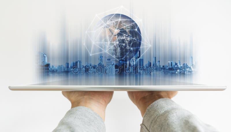 Dé sostener la tableta digital con tecnología de la conexión de red global y el holograma moderno de los edificios El elemento de fotografía de archivo libre de regalías
