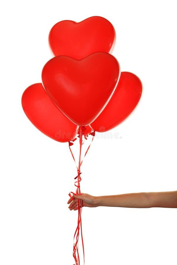 Dé sostener los globos de un corazón del rojo aislados en un blanco fotos de archivo