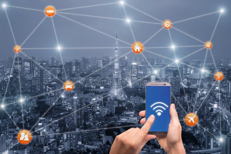 Dé sostener smartphone con el scape de la ciudad de Tokio y la red del wifi imagen de archivo