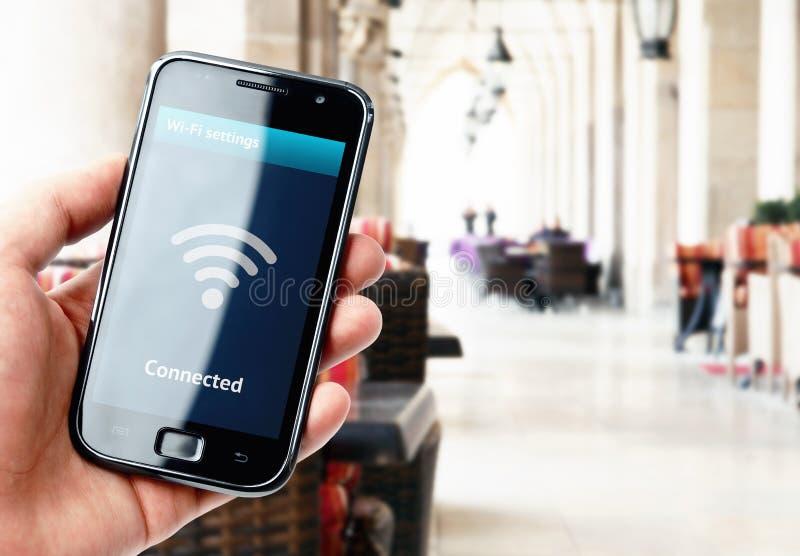 Dé sostener smartphone con la conexión de Wi-Fi en café imagen de archivo