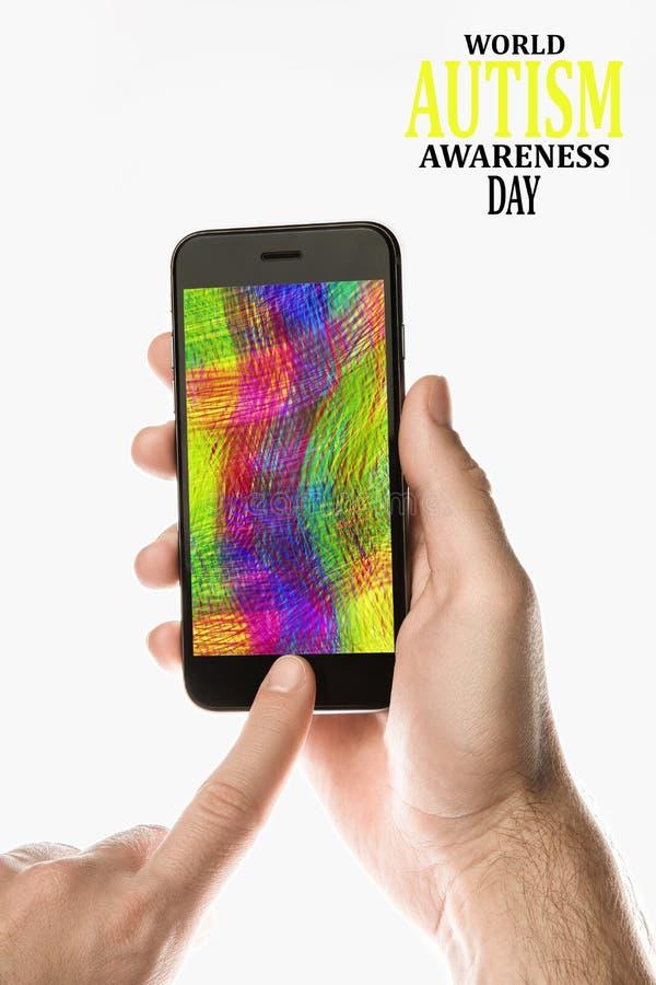 Dé sostener Smartphone negro con la pantalla a color en el backgro blanco foto de archivo libre de regalías