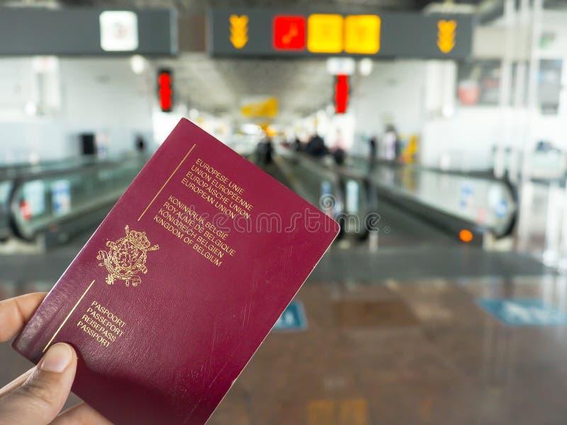 Dé sostener un pasaporte belga mientras que camina en un aeropuerto foto de archivo