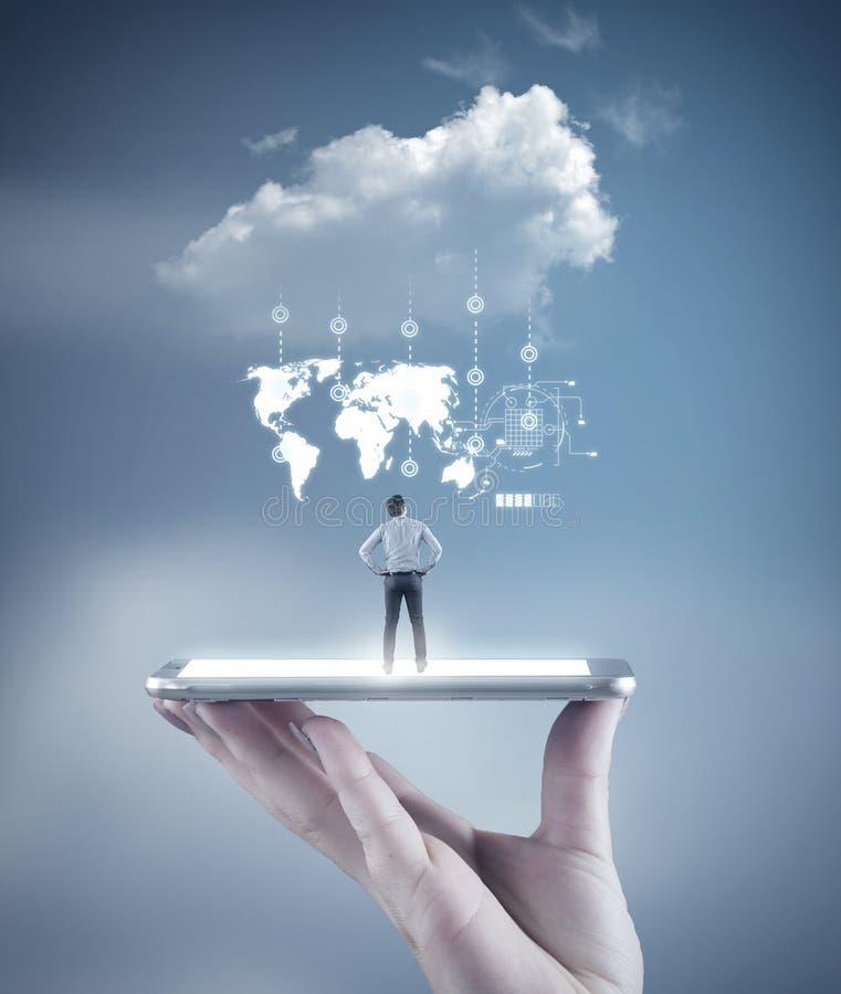 Dé sostener un smartphone con un hombre de negocios que mira para arriba a la nube imagen de archivo