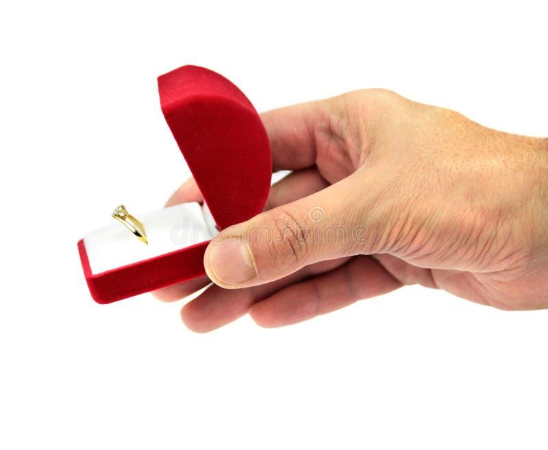 Dé sostener una caja de regalo roja con el anillo de bodas imagenes de archivo