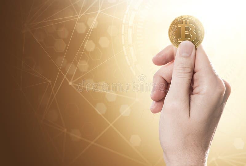 Dé sostener una moneda del efectivo de Bitcoin en un fondo brillante con la red del blockchain Copie el espacio incluido foto de archivo libre de regalías