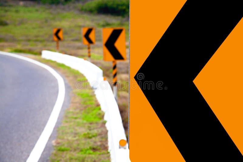 Dé vuelta a la señal de peligro izquierda del camino imagen de archivo