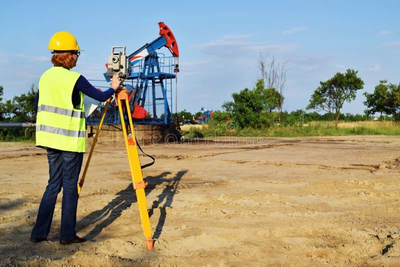 Débarquez l'expert en matière d'arpenteur au travail sur un puits de pétrole photo stock