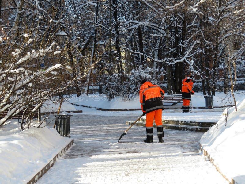 Déblaiement de neige, neige claire de travailleurs communaux de services avec une pelle photos libres de droits