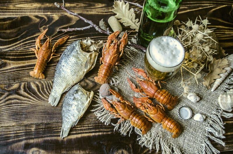 Débordement avec le verre spongieux avec de la bière et une bouteille de bière et d'écrevisses rouges bouillies salées photographie stock libre de droits