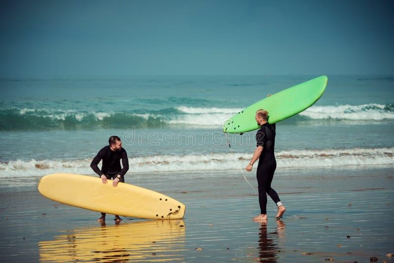 Débutant et instructeur de surfer sur une plage avec conseils surfants images stock
