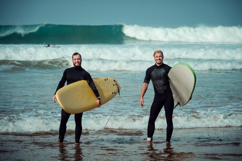 Débutant et instructeur de surfer sur une plage avec planches de surf image stock
