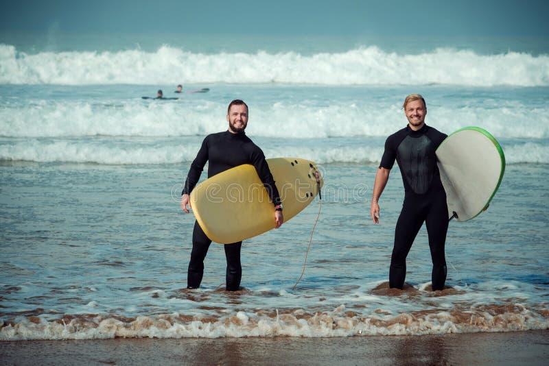 Débutant et instructeur de surfer sur une plage avec planches de surf image libre de droits