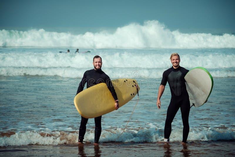 Débutant et instructeur de surfer sur une plage avec planches de surf photo libre de droits