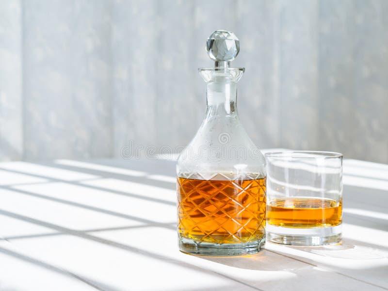 Décanteur et roches de whiskey en verre par la fenêtre images libres de droits