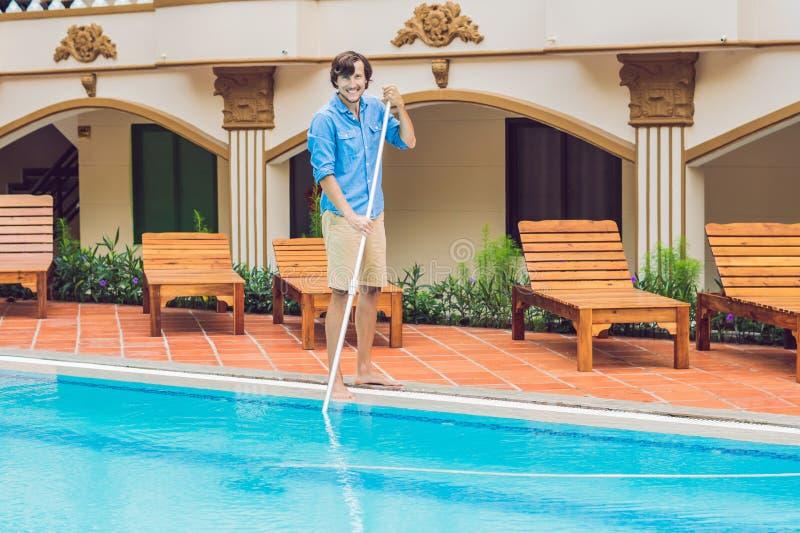 Décapant de la piscine Homme dans une chemise bleue avec l'équipement de nettoyage pour des piscines, ensoleillé photos stock