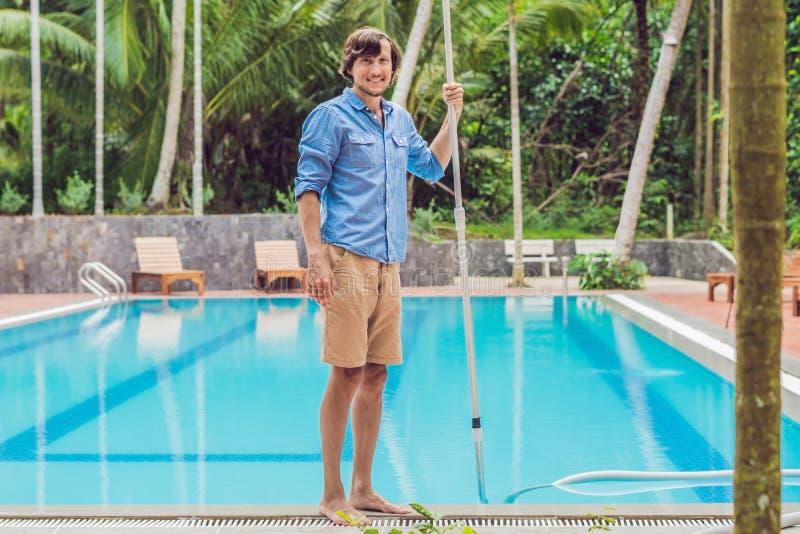 Décapant de la piscine Homme dans une chemise bleue avec le nettoyage photographie stock libre de droits