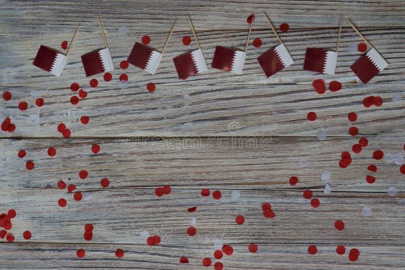 18 décembre fête de l'indépendance du Qatar mini drapeaux sur fond de bois avec confettis en papier jour heureux du patriotisme images libres de droits