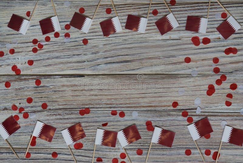 18 décembre fête de l'indépendance du Qatar mini drapeaux sur fond de bois avec confettis en papier jour heureux du patriotisme photographie stock libre de droits