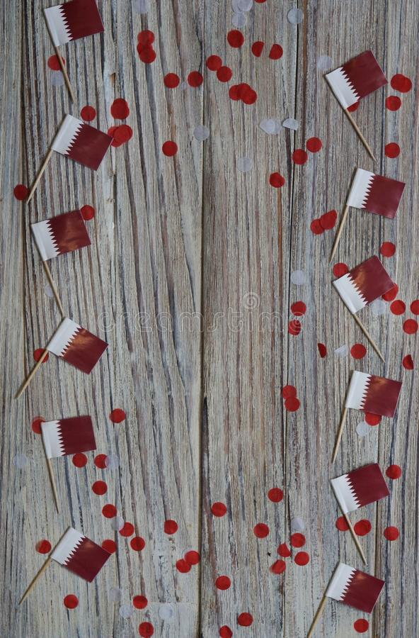 18 décembre fête de l'indépendance du Qatar mini drapeaux sur fond de bois avec confettis en papier jour heureux du patriotisme photos stock