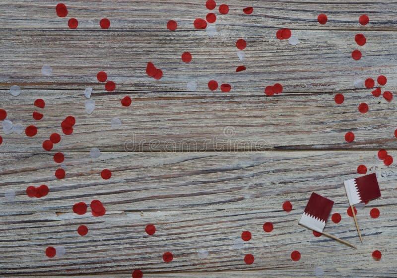 18 décembre fête de l'indépendance du Qatar mini drapeaux sur fond de bois avec confettis en papier jour heureux du patriotisme photo libre de droits