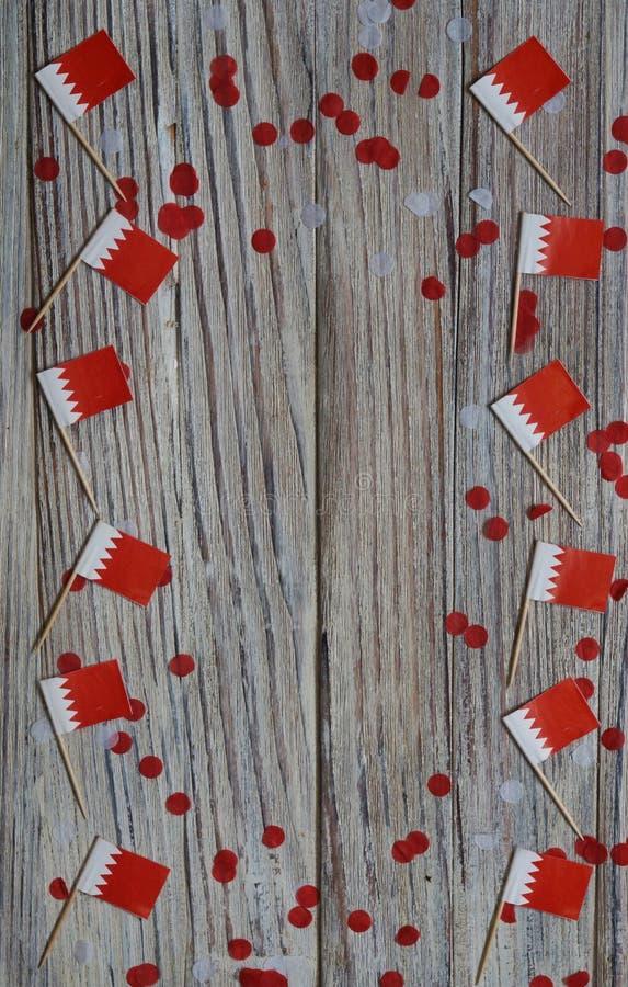 16 décembre Jour de l'indépendance de Bahreïn mini drapeaux sur fond de bois avec confettis en papier jour heureux du patriotisme photo libre de droits