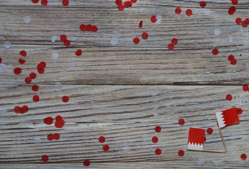 16 décembre Jour de l'indépendance de Bahreïn mini drapeaux sur fond de bois avec confettis en papier jour heureux du patriotisme images stock