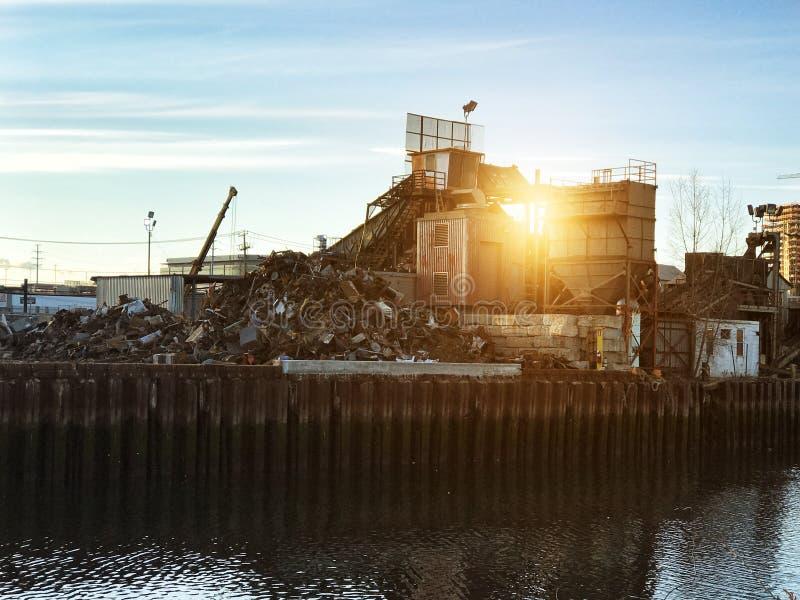 Décharge de mitraille de voiture réutilisant l'usine industrielle au temps de coucher du soleil photo stock