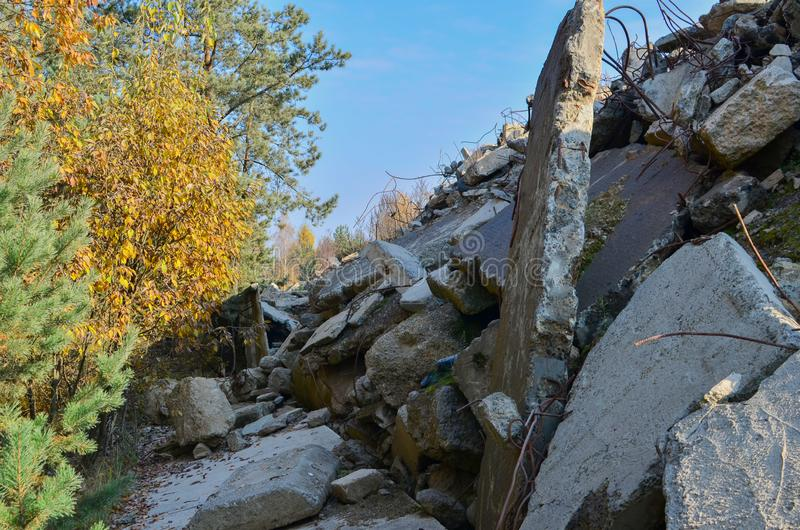 déchets, blocs de béton renforcés et garnitures rouillées Tas des blocs de béton, des piles et des tuyaux endommagés image libre de droits