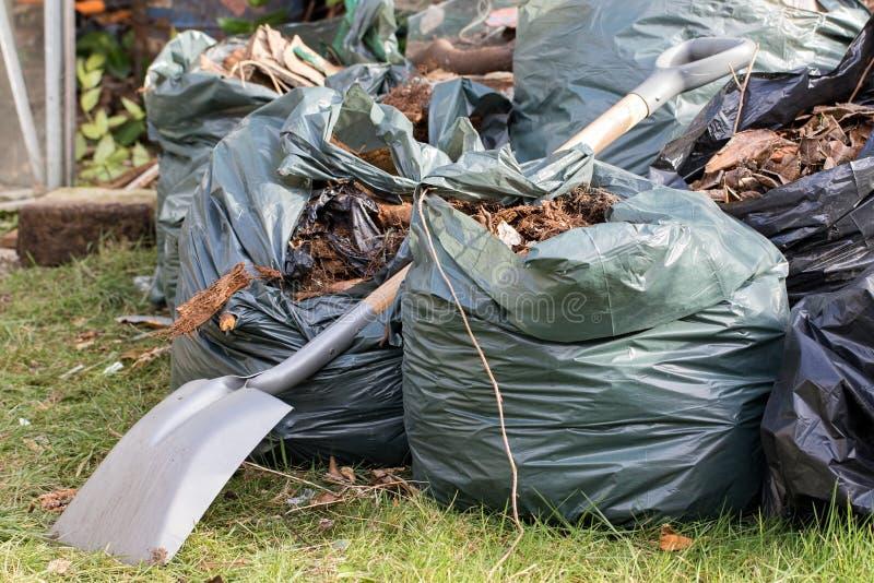 Déchets de jardin Feuilles et déchets de Brown rassemblés du jardinage rangé image libre de droits