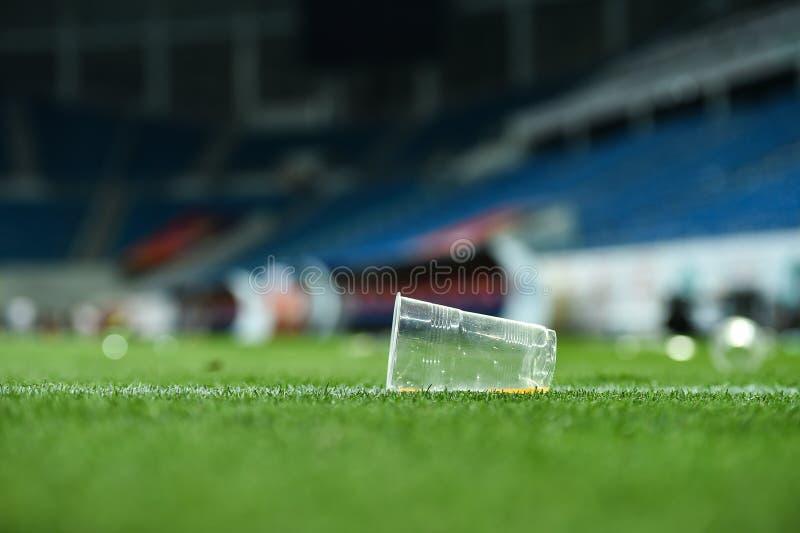 Déchets en plastique sur le gazon sur un terrain de football images stock