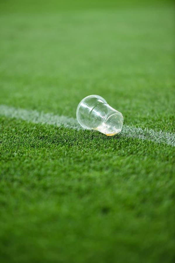 Déchets en plastique sur le gazon sur un terrain de football photos stock