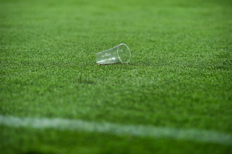 Déchets en plastique sur le gazon sur un terrain de football image libre de droits