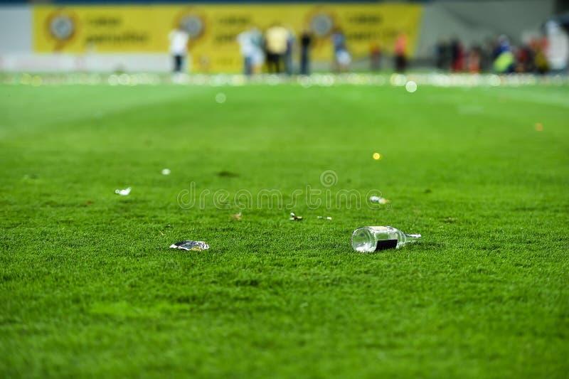 Déchets en plastique sur le gazon sur un terrain de football photographie stock libre de droits