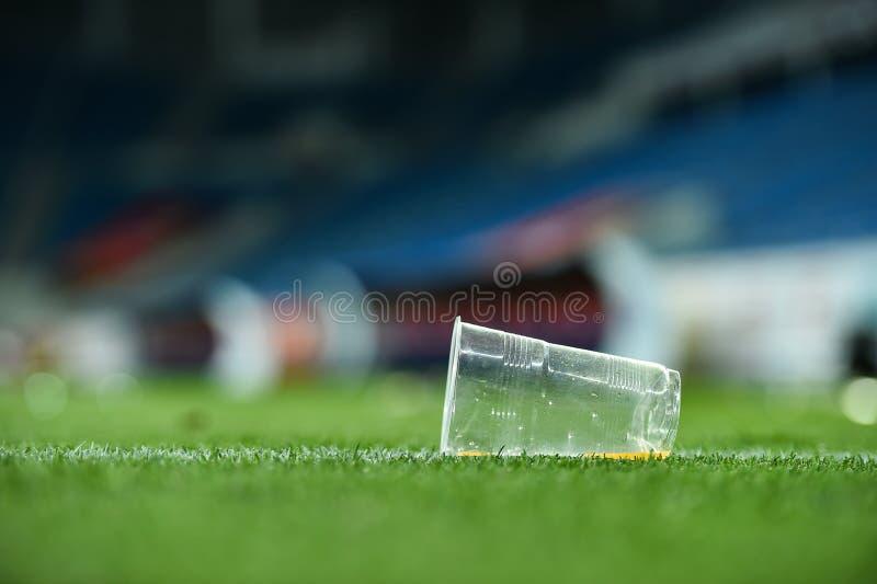 Déchets en plastique sur le gazon sur un terrain de football photographie stock