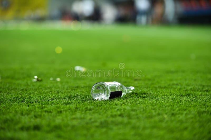 Déchets en plastique sur le gazon sur un terrain de football photo stock