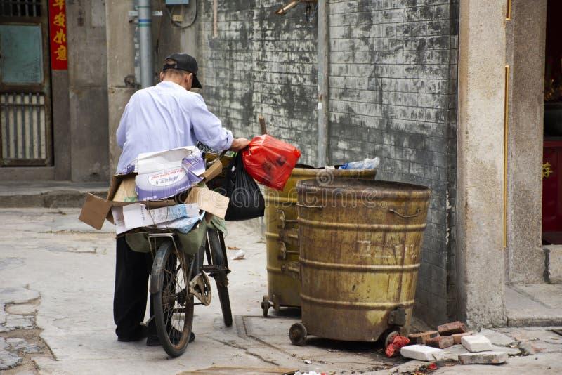 Déchets recyclables chinois de découverte et de collecte de gardien de déchets de vieil homme dans la poubelle de déchets au pani image libre de droits