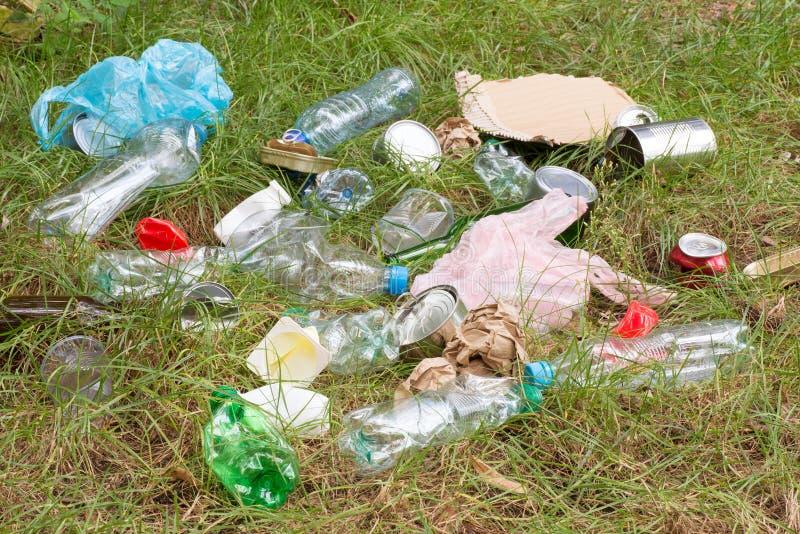 Déchets tels que les bouteilles en plastique et en verre, les boîtes, les boîtes et les morceaux de papier sur l'herbe images stock
