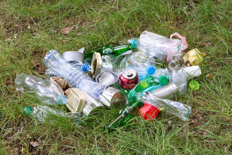 Déchets tels que les bouteilles en plastique et en verre, les boîtes, les boîtes et les morceaux de papier sur l'herbe photos libres de droits