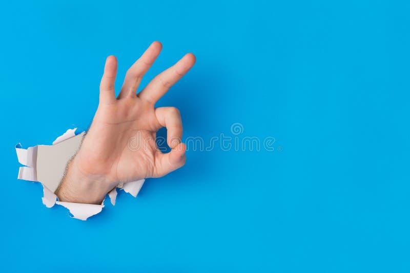 Déchirure de main masculine à travers un fond de papier bleu créant un geste OK photographie stock