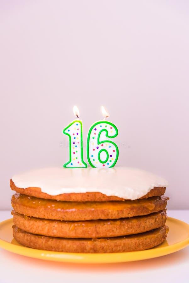 Décimosextas velas del cumpleaños en fondo rústico del pastel de la torta acodada del vegano imagen de archivo libre de regalías