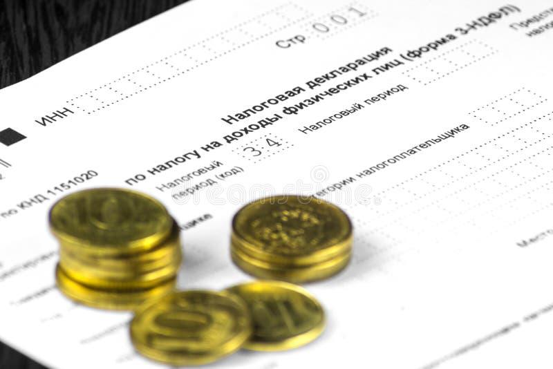 Déclaration annuelle russe d'impôts des impôts des personnes La forme 3-NDFL Quelques pièces de monnaie russes sont sur la feuill photographie stock libre de droits