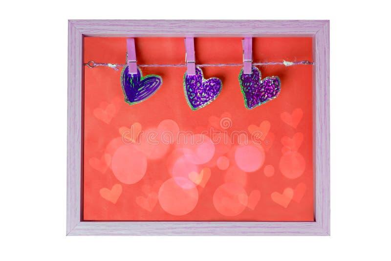 Déclaration de l'amour avec trois coeurs décoratifs sur un chlothesline dans un cadre en bois avec la texture rouge de fond d'iso photographie stock libre de droits