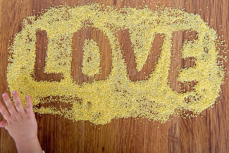 Déclaration de millet peint par amour L'enfant dessine sur une table avec le millet de croustillants images libres de droits