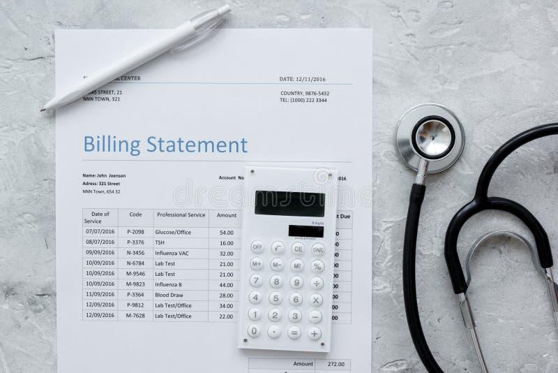 Déclaration treatmant médicale de facturation avec le stéthoscope et la calculatrice sur la vue supérieure de fond en pierre image stock