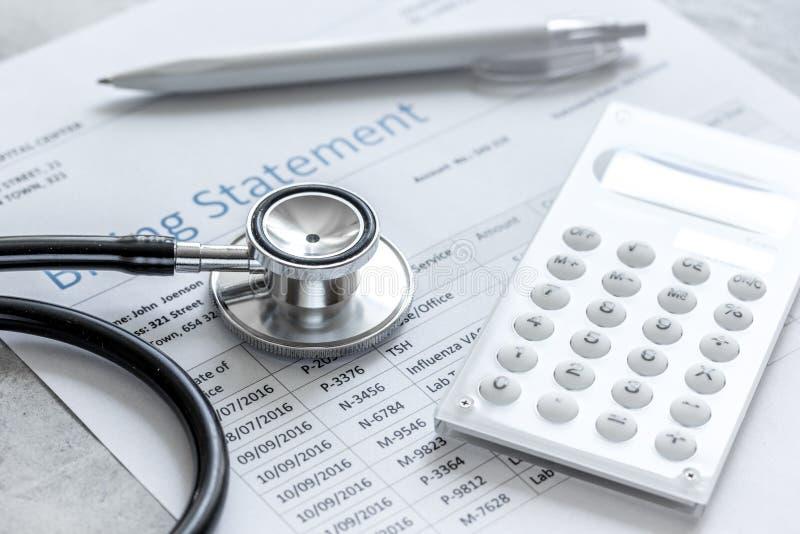 Déclaration treatmant médicale de facturation avec le stéthoscope et la calculatrice sur le fond en pierre photo libre de droits